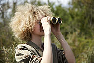 Young woman with curly hair looking through old binoculars - TSFF00200