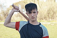 Portrait of young man with baseball bat in park - RTBF01077