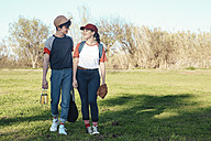 Smiling young couple with baseball equipment walking in park - RTBF01080