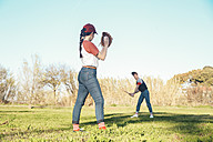 Young couple playing baseball in park - RTBF01089