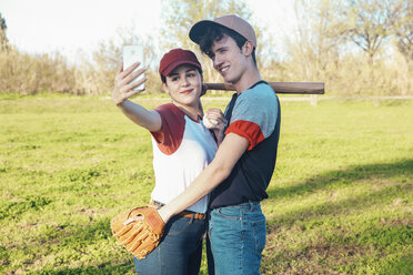 Smiling young couple with baseball equipment taking a selfie in park - RTBF01092