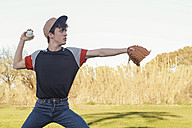 Young man playing baseball in park - RTBF01095