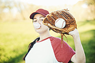 Portrait of young woman with ball and baseball glove blowing a gum bubble - RTBF01098