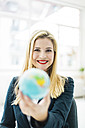 Portrait of smiling businesswoman holding mini globe - MOEF00219