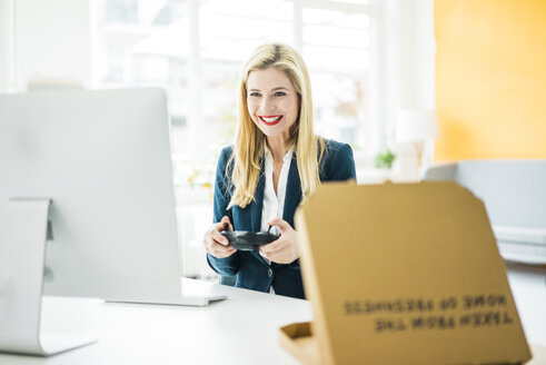 Smiling businesswoman using controller at desk in office - MOEF00222