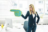 Confident businesswoman pointing with large hand in office - MOEF00225
