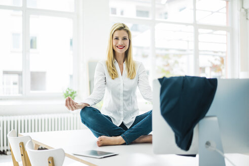 Smiling businesswoman sitting on desk in office practicing yoga - MOEF00228
