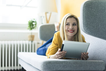 Woman lying on couch using tablet - MOEF00234
