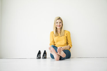 Relaxed smiling woman sitting on floor - MOEF00237