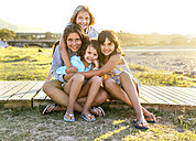 Group picture of four girls sitting on boardwalk in summer - MGOF03669