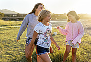 Four girls playing outdoors at sunset girls on boardwalk - MGOF03675