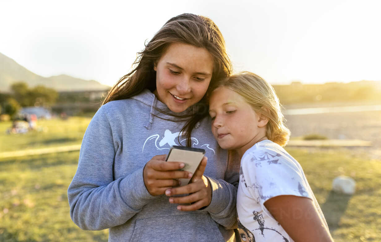 Two girls looking at cell phone outdoors - MGOF03678 - Marco Govel/Westend61