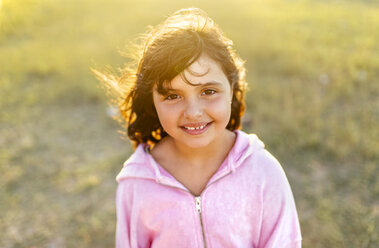 Portrait of smiling little girl with blowing hair at backlight - MGOF03681