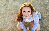 Portrait of smiling girl at twilight looking up - MGOF03684