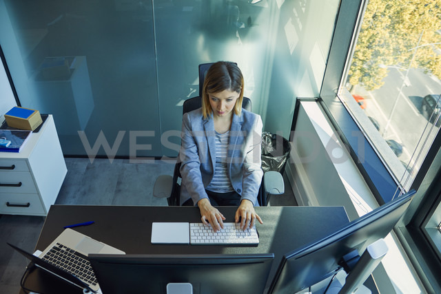 Businesswoman using computer in office - ZEDF00928 - Zeljko Dangubic/Westend61