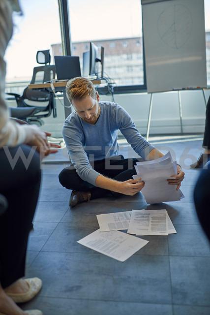 Businessman organising papers on the floor in office - ZEDF00946