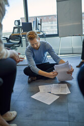 Businessman organising papers on the floor in office - ZEDF00946