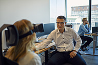 Man looking at woman wearing VR glasses in office - ZEDF00955