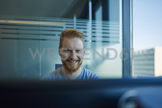 Happy businessman at desk in office - ZEDF00961
