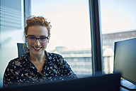Smiling businesswoman working in office - ZEDF00967