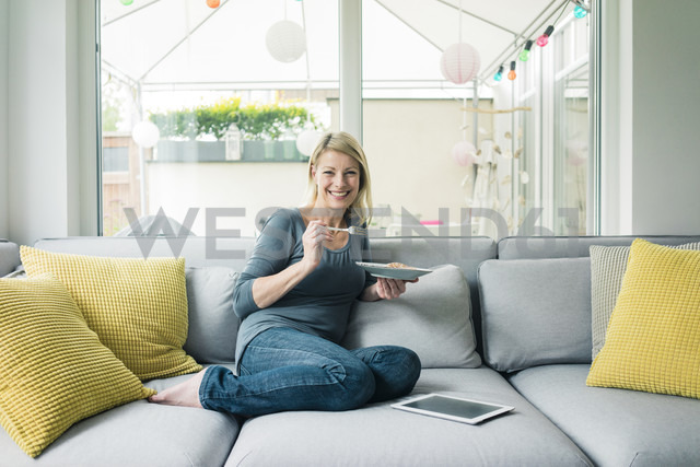 Portrait of happy woman relaxing on couch - MOEF00243