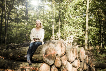Portrait of woman sitting on stack of logs in the forest with tablet - MOEF00252