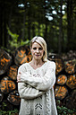 Portrait of blond woman at stack of logs in the forest - MOEF00255