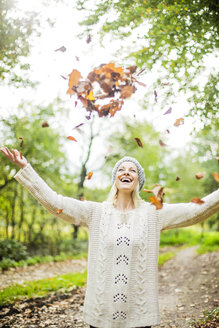 Happy woman in the forest in autumn throwing leaves in the air - MOEF00258