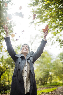 Happy woman in the forest in autumn throwing leaves in the air - MOEF00261