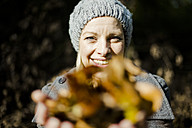 Portrait of happy woman in the forest in autumn holding leaves - MOEF00264