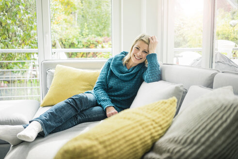 Portrait of happy woman relaxing on couch - MOEF00267