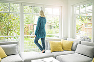Woman in living room looking out of window - MOEF00270