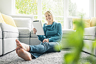 Happy woman using tablet in living room - MOEF00273