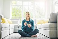 Portrait of happy woman eating muesli in living room - MOEF00276