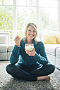Portrait of happy woman eating fruit yoghurt in living room - MOEF00279