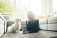 Happy woman with dog in living room - MOEF00282