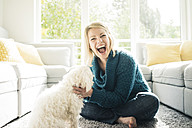 Playful woman with her dog in living room - MOEF00285