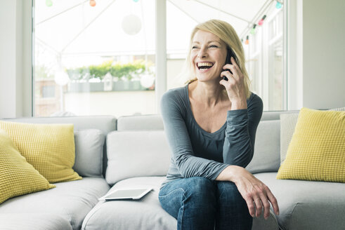 Happy woman on the phone on couch - MOEF00288