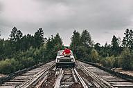 Man sitting on car bonnet on wooden lane in rural landscape - VPIF00235
