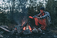 Man sitting at campfire in rural landscape - VPIF00241