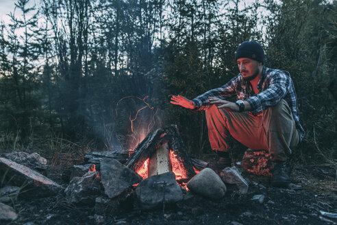 Man sitting at campfire in rural landscape - VPIF00241