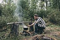 Man cooking in cauldron in rural landscape - VPIF00259
