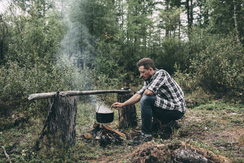 Man cooking in cauldron in rural landscape - VPIF00259
