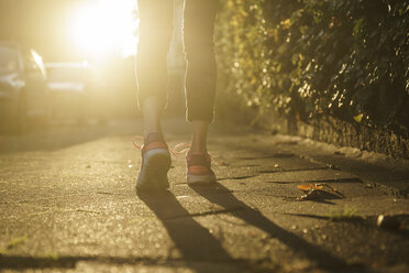 Legs of woman jogging on walkway at sunset - CHPF00447