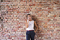 Businesswoman using cell phone at brick wall - HAPF02346