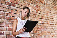 Businesswoman holding clipboard at brick wall in office - HAPF02349