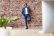 Businessman using cell phone at brick wall - HAPF02352