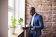 Businessman using cell phone at brick wall by the window - HAPF02355