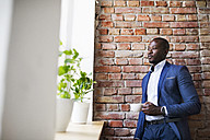 Businessman with cup of coffee at brick wall by the window - HAPF02358