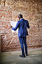 Businessman studying plan at brick wall - HAPF02364